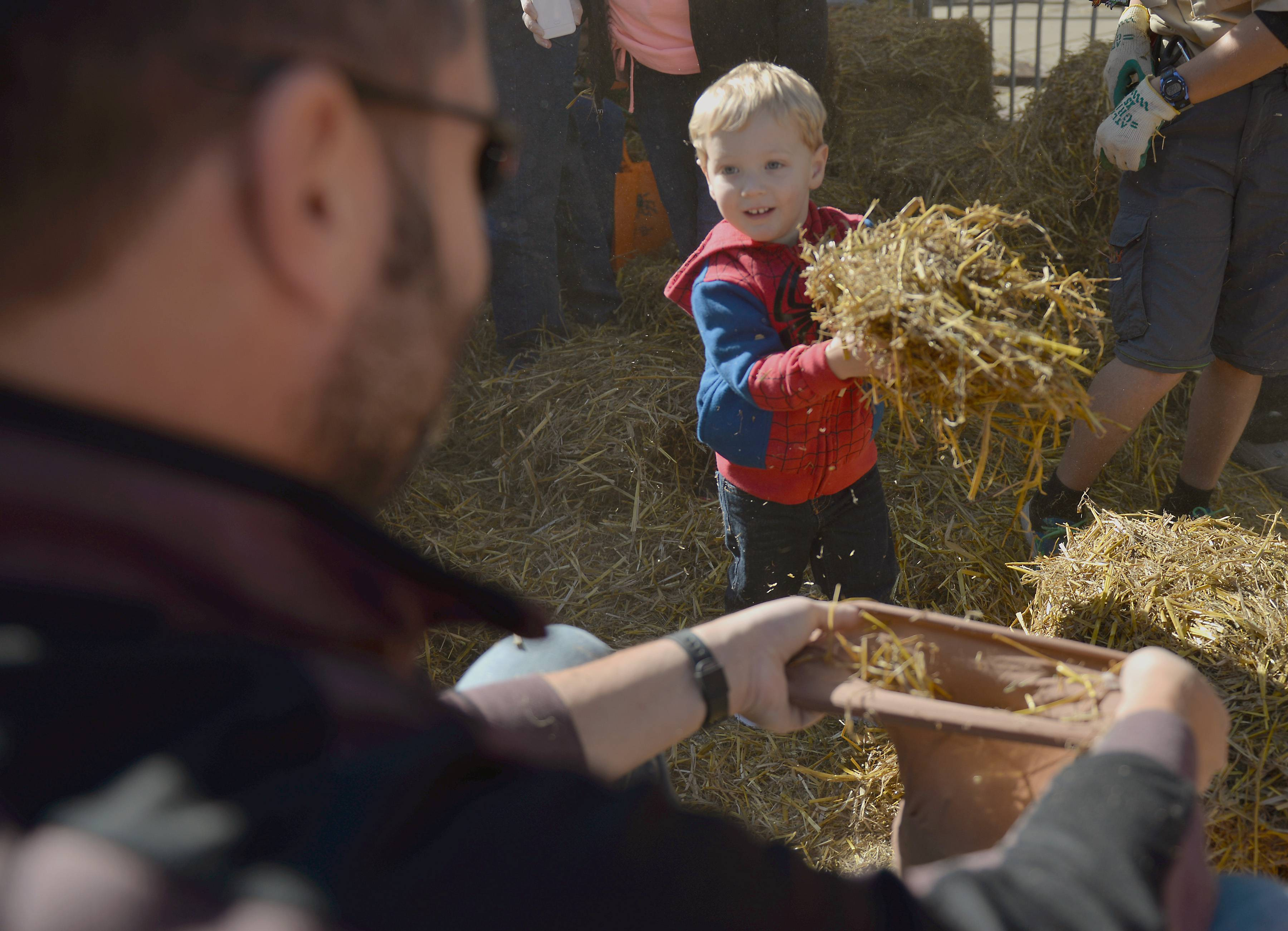 Seth Bone, 2, helps his father Brian stuff a scarecrow Saturday at St. Charles Scarecrow Fest.