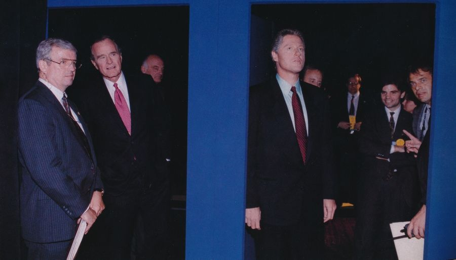 White House advance office director Ed Murnane consults with President George H.W. Bush before a debate Oct. 15, 1992, while in a room on the left challenger Bill Clinton peers out at the stage.