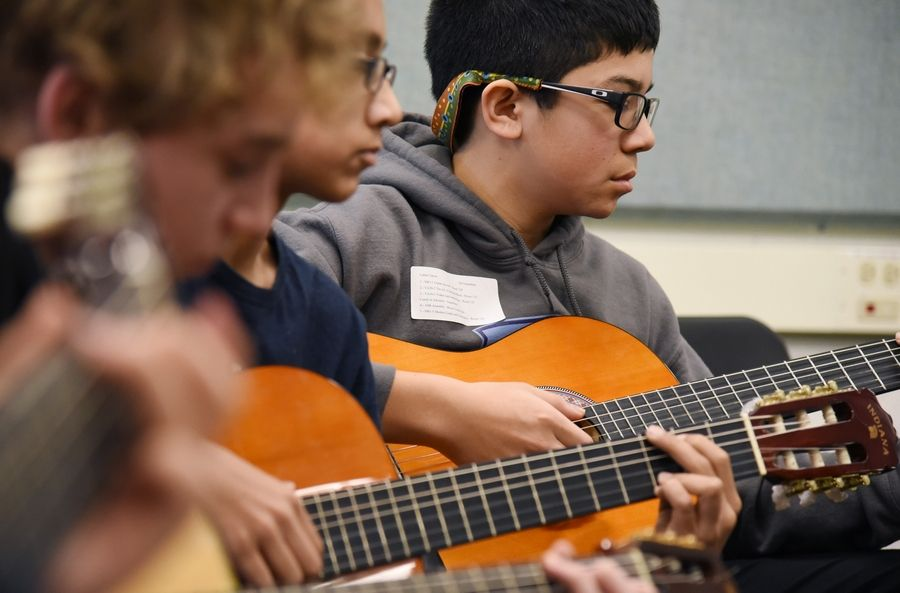Daniel Wright Junior High School seventh-grader Lukas Garcia participates in the Guitar Anyone? session at the Explore the Arts day in Lincolnshire. Suburban educators say a new federal law that goes into effect next school year should measure schools by more than test scores and consider programs such as fine arts to measure improvement.