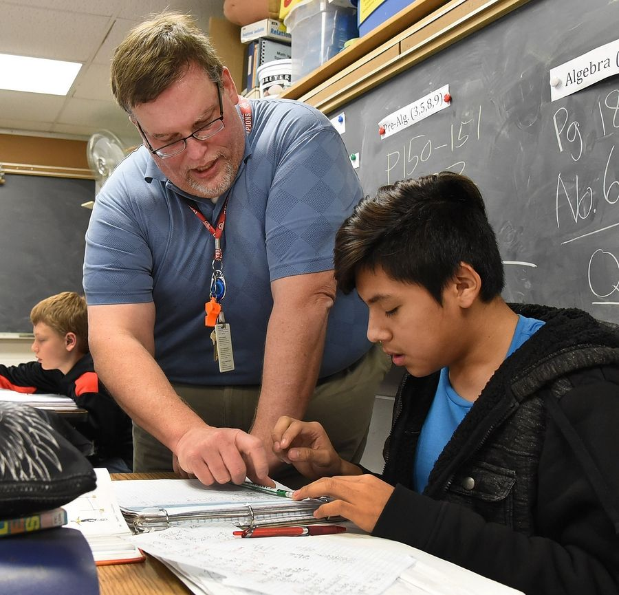 David Keller helps Dennis Gonzalez in his seventh-grade math class at Thomas Middle School in Arlington Heights. Suburban educators say a new federal law that goes into effect next school year should measure schools by more than test scores and consider programs such as science, technology, engineering and math (STEM) education to measure improvement.