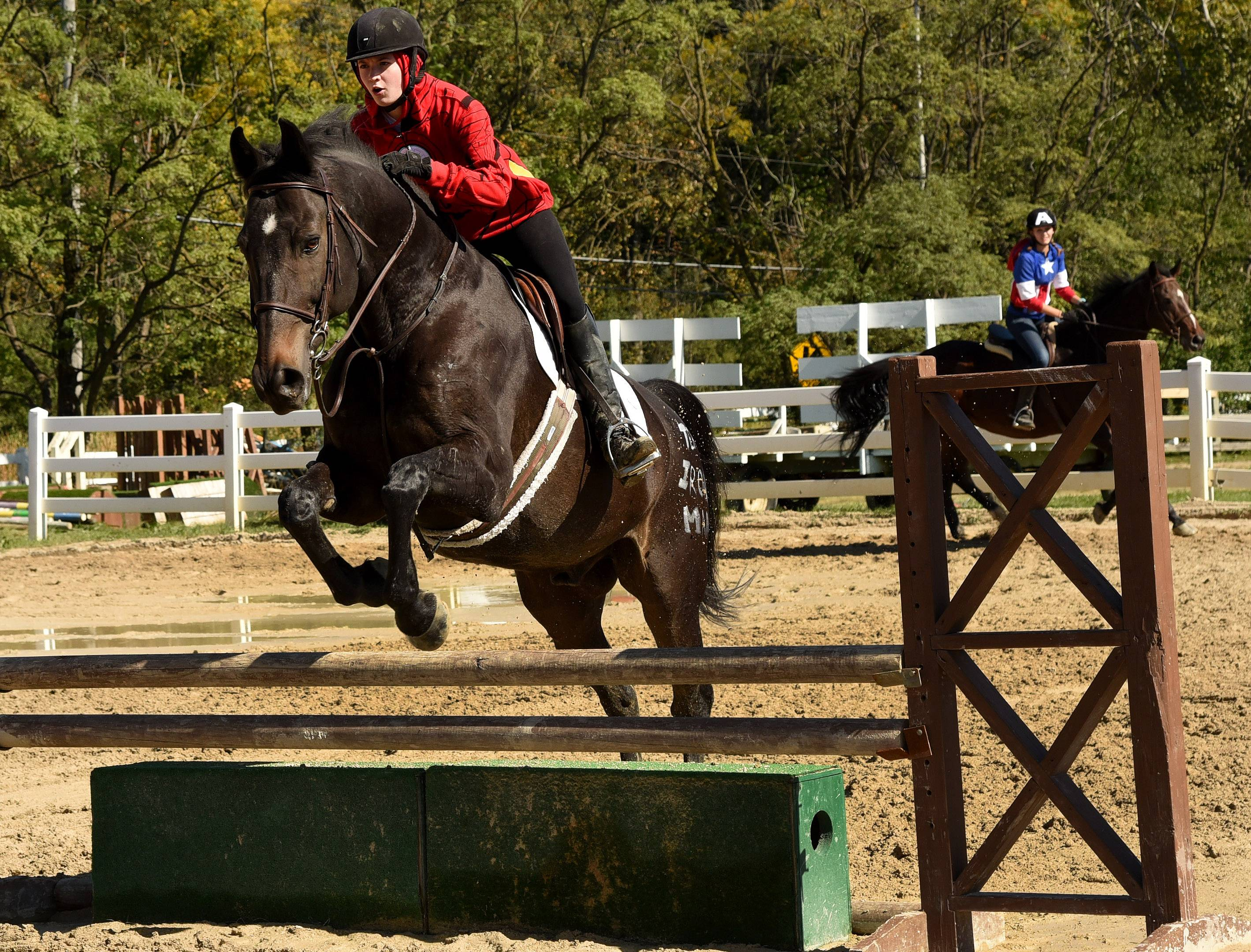 Haley Farrahar makes a jump with Goliath, with Lizzie Gaare riding Guiness trailing behind, during a riding exhibition at Palatine Stables Fall Festival.