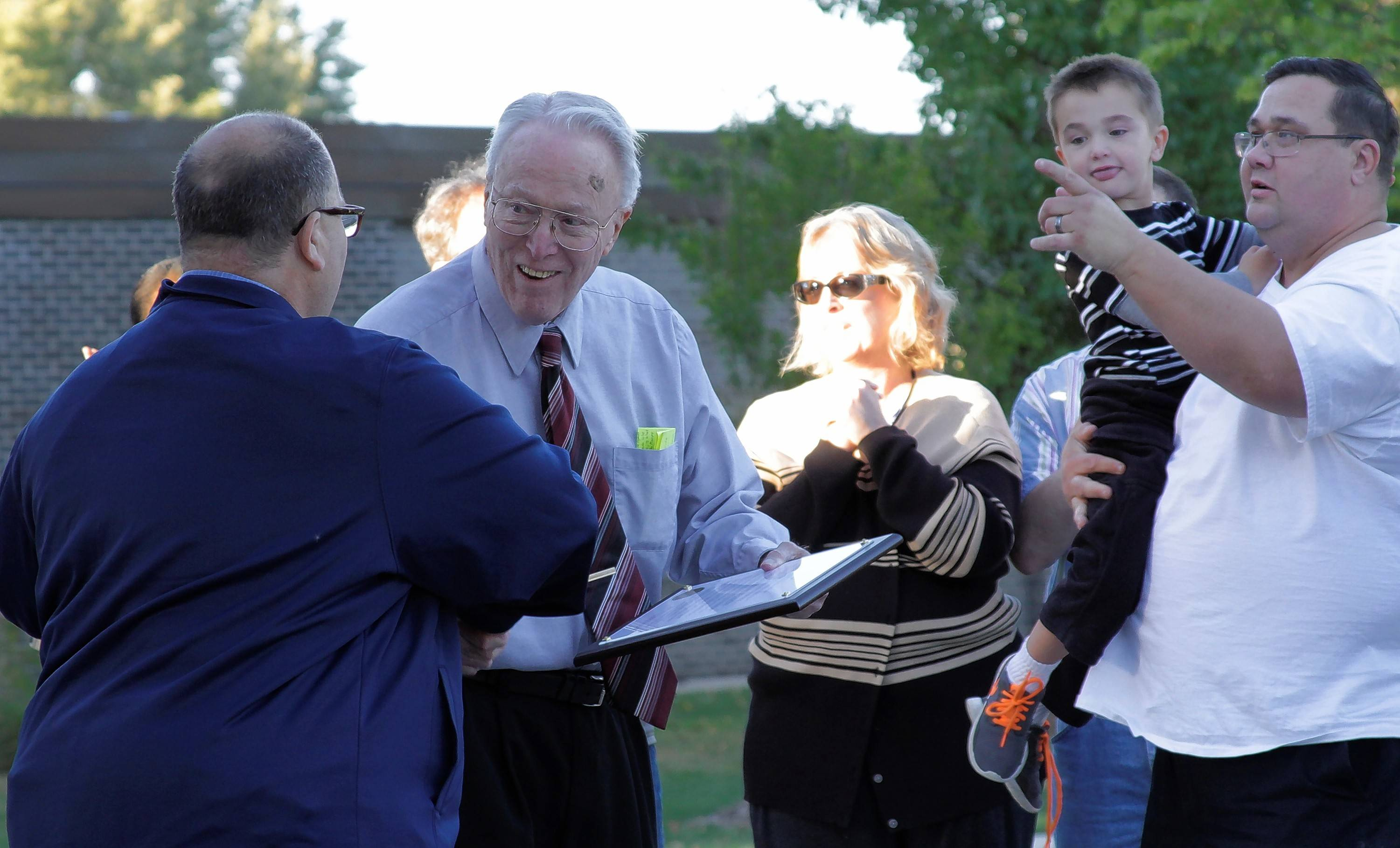 Buffalo Grove Park Board President Rick Drazner shakes hands with Bill Kiddle as his oldest daughter, Bonnie Kathleen Doucet, grandson Aidan Doucet, and son-in-law Al Doucet look on.