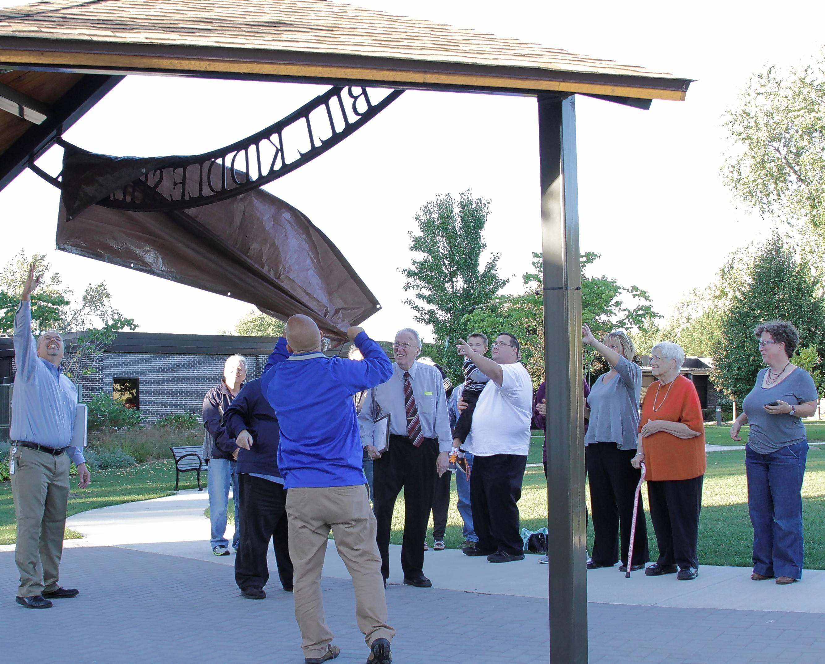 Buffalo Grove Park District officials unveil the sign naming the new shelter in front of the Alcott Center in honor of longtime board member Bill Kiddle, 84.