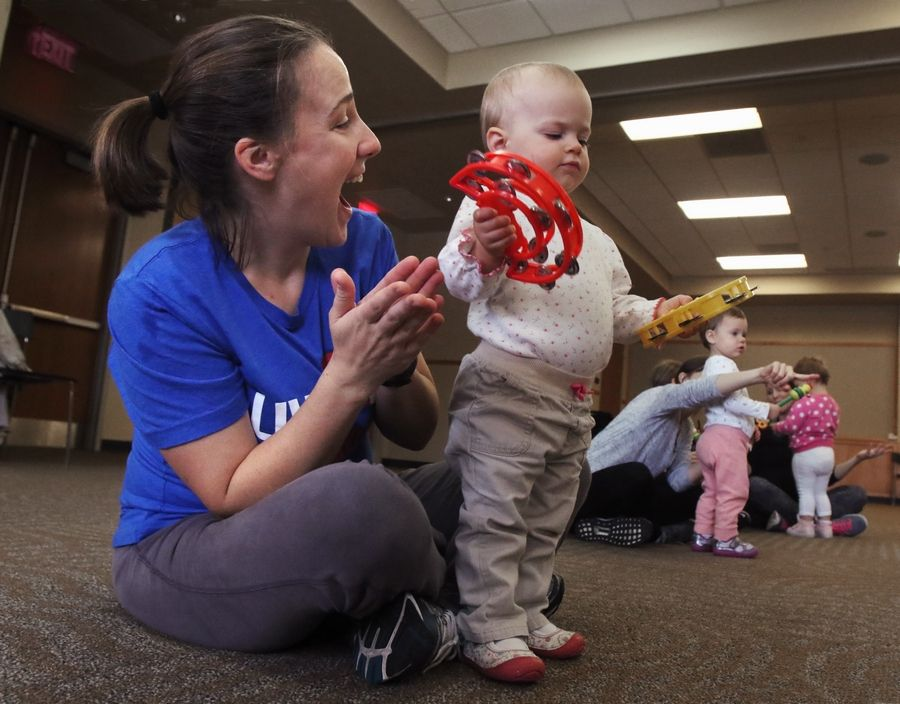 Cathy Molloy of Lake Zurich watches her 20-month-old daughter, Faith, play with toy tambourines during Wednesday's Zumbini class at Ela Area Public Library in Lake Zurich. Zumba instructor C. Rene Collins-Maragh used dance and music to create a bonding experience for mothers or caregivers and their children, ages 3 months to 3 years old.