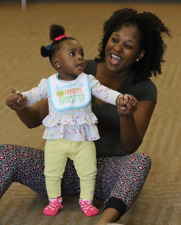 Victoria Obianwu of Lake Zurich dances with her 10-month-old daughter, Kosi, during Wednesday's Zumbini class at Ela Area Public Library in Lake Zurich. Zumba instructor C. Rene Collins-Maragh used dance and music to create a bonding experience for mothers or caregivers and their children, ages 3 months to 3 years old.