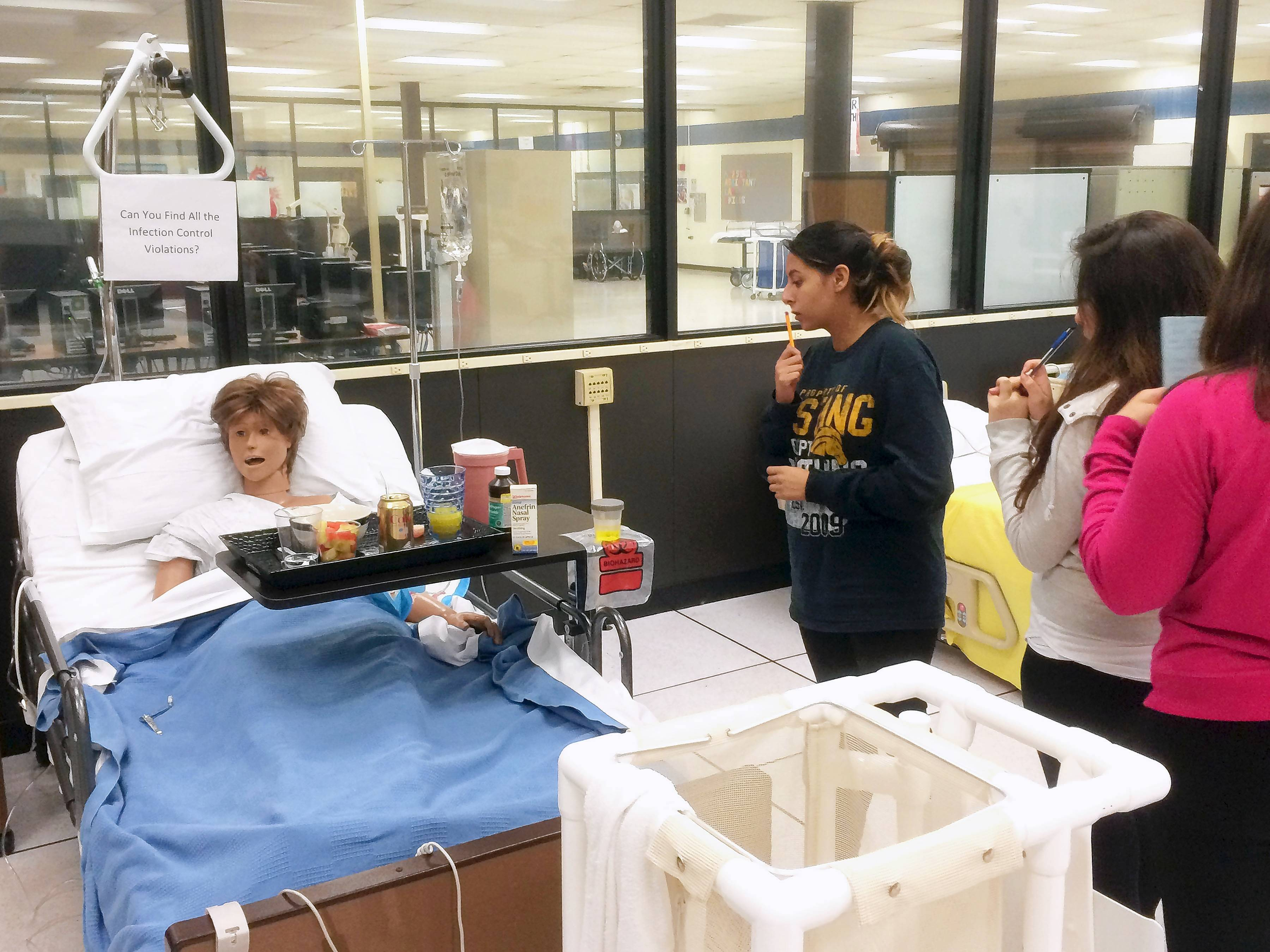 "Nursing assistant students at Technology Center of DuPage visit a ""patient"" in the program's lab. Their lesson is to find all the infection control violations of this scenario."