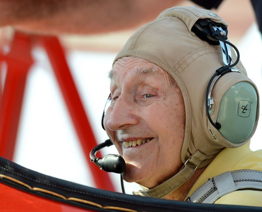 John Carlson, 90, of Batavia smiles from the front seat of a Stearman biplane as his wife, Dorothy, takes a picture.