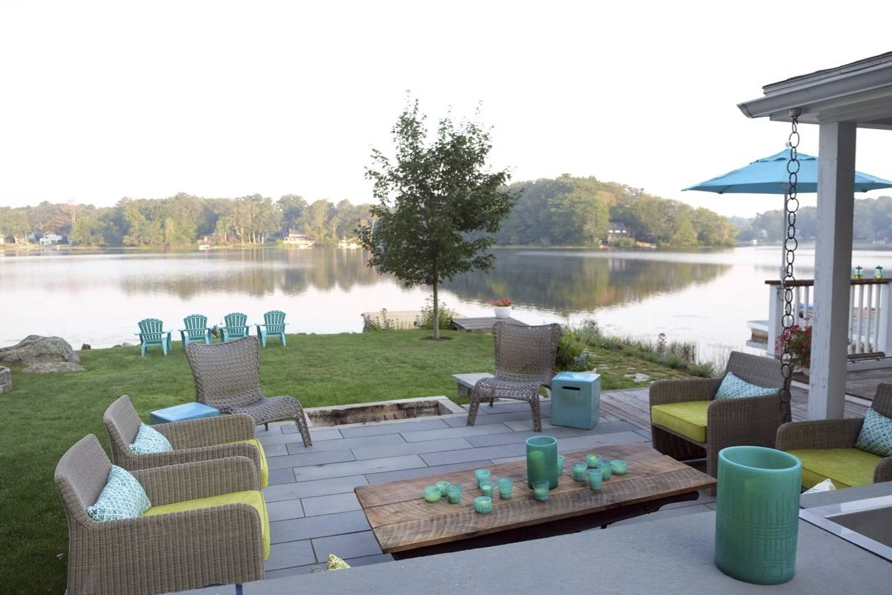 This summer entertaining space can easily be used during colder fall weather with the help of a large fire pit near the lawn.