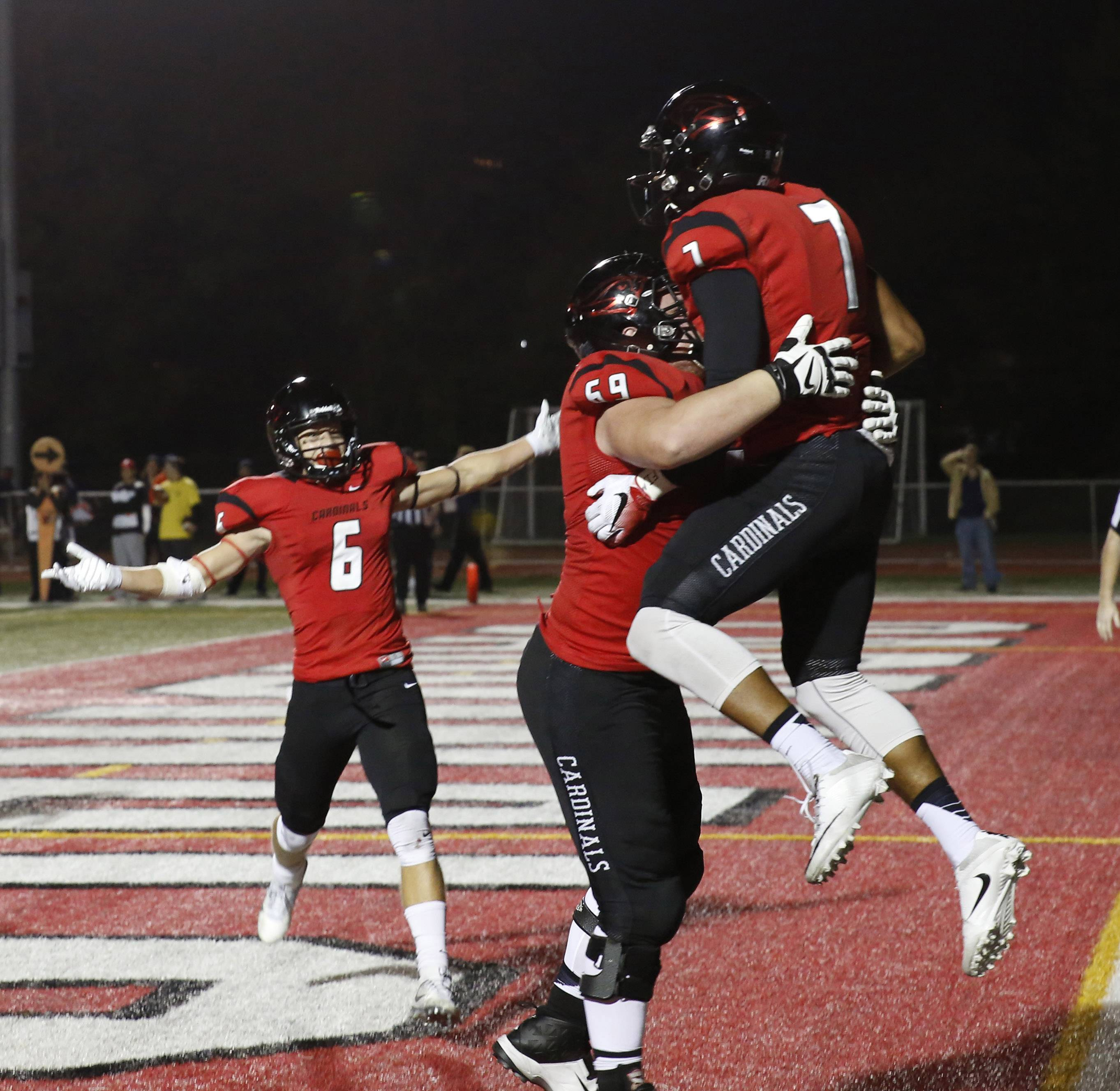 North Central College's Dylan Warden (7) celebrates scoring a fourth quarter touchdown over Wheaton College with Nathan Palermo (59) and Alex Ulmer (6) in Naperville.