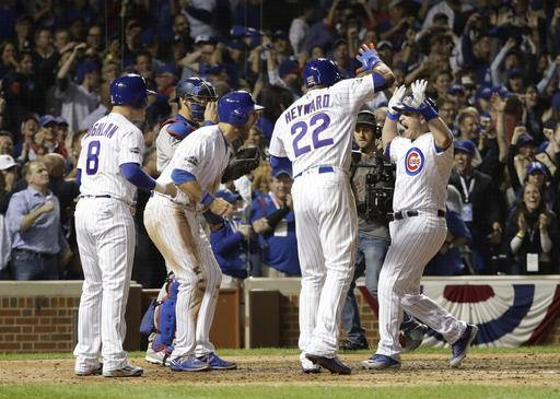 Chicago Cubs catcher Miguel Montero, right, celebrates after hitting a grand slam during the eighth inning of Game 1 of the National League baseball championship series against the Los Angeles Dodgers Saturday, Oct. 15, 2016, in Chicago.