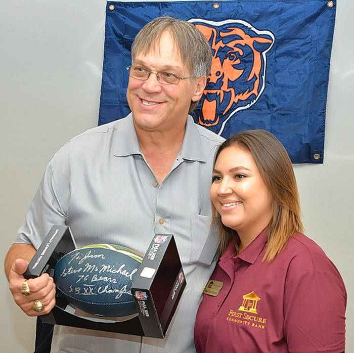 Montgomery resident Samantha Clifton, right, poses with retired Chicago Bear Steve McMichael Oct. 8 at First Secure Community Bank of Aurora in Aurora. Clifton is a universal banker at First Secure. McMichael appeared during the bank's grand opening.