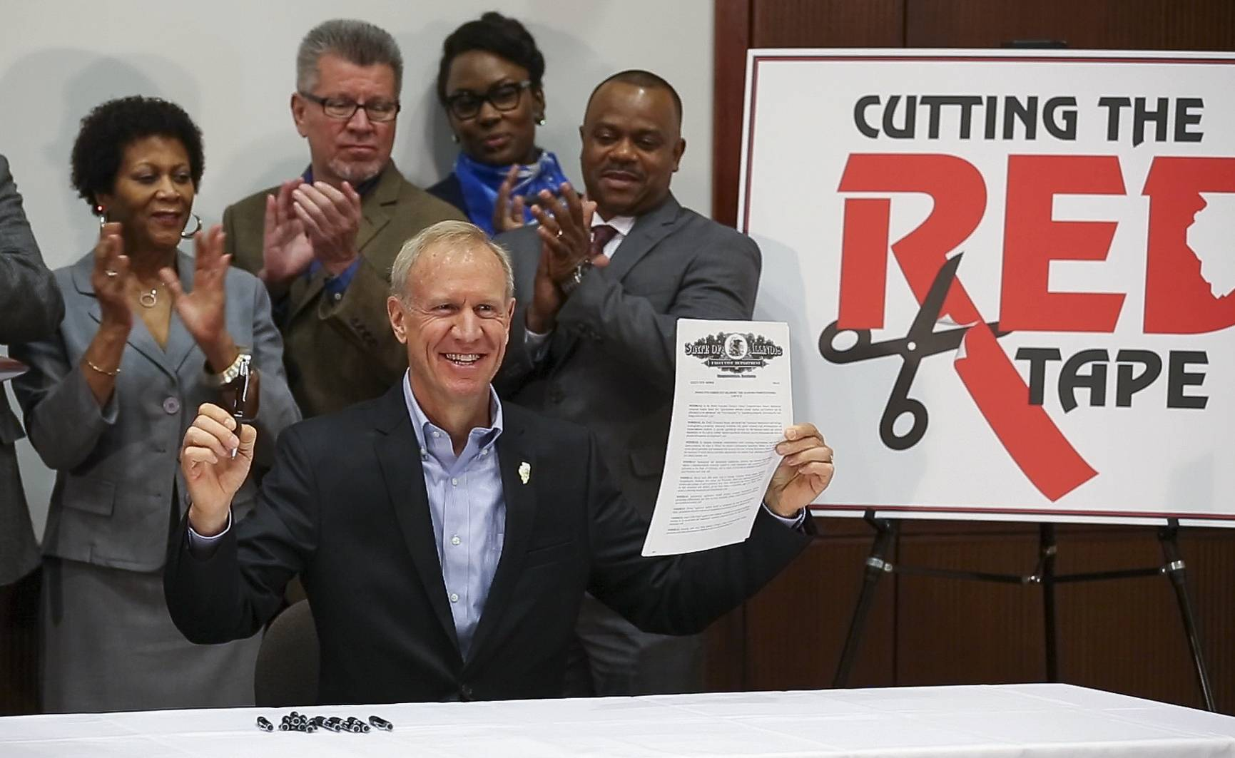 Gov. Bruce Rauner signs an executive order that he says is designed to cut red tape and grow the economy during a news conference Monday at the College of DuPage.