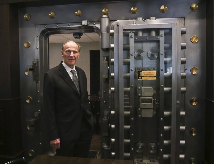 Claude Gendreau, 75, is a veterinary surgeon in Buffalo Grove, who owns and operates the Ravisloe Country Club, the La Banque Hotel and La Voute Bistro Bar at the hotel, all in Homewood. Here, he stands in an old bank vault in the cafe. At right, the La Banque Hotel and La Voute Bistro Bar.