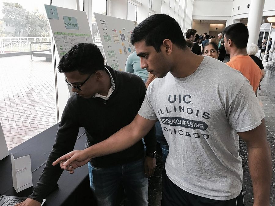 University of Illinois-Chicago students Omar Maldonado, left, and Mohiuddin Ahmed, of Hanover Park, stand over their third-place winning presentation Sunday at the AMITA Health Design Challenge in Arlington Heights.