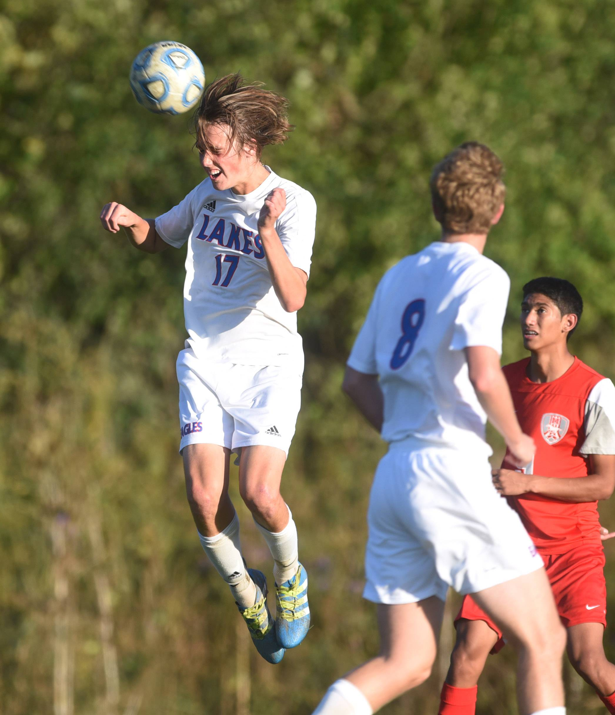 Lakes' Max Keenan (17) goes for a header during Tuesday's home soccer game against Mundelein in Lake Villa.