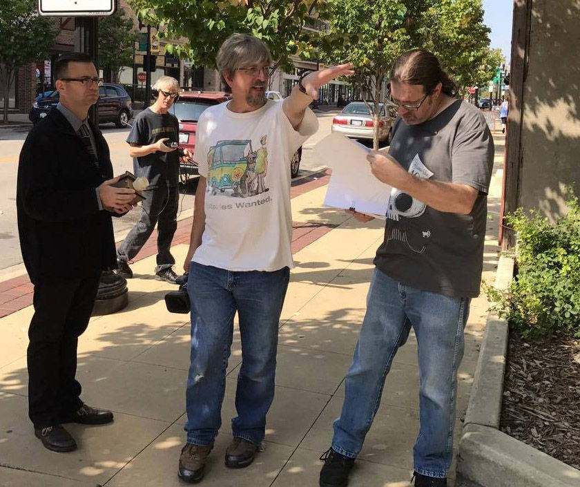 Actor Rich Jacobs, from left, with sound technician Willy Deal in the background, and co-directors Jeff Kelley and Dave Metzger while filming in downtown Elgin.
