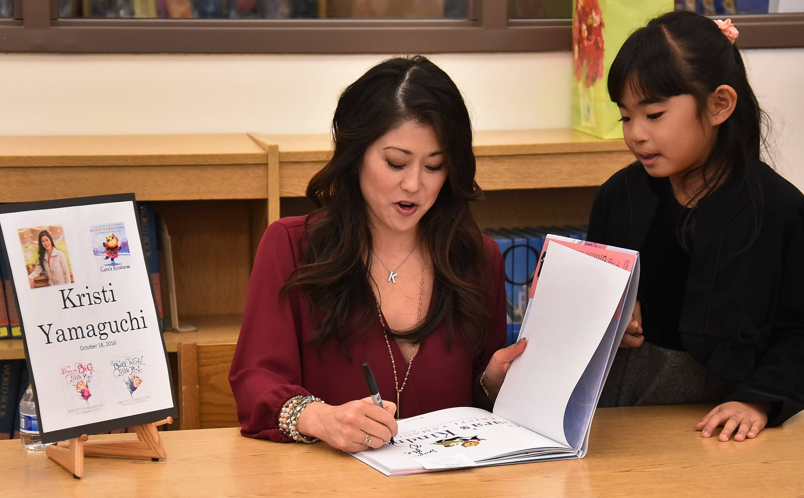 "Olympic figure skater Kristi Yamaguchi signs her latest children's book, ""Cara's Kindness,"" for students Tuesday at Frank C. Whiteley School in Hoffman Estates."