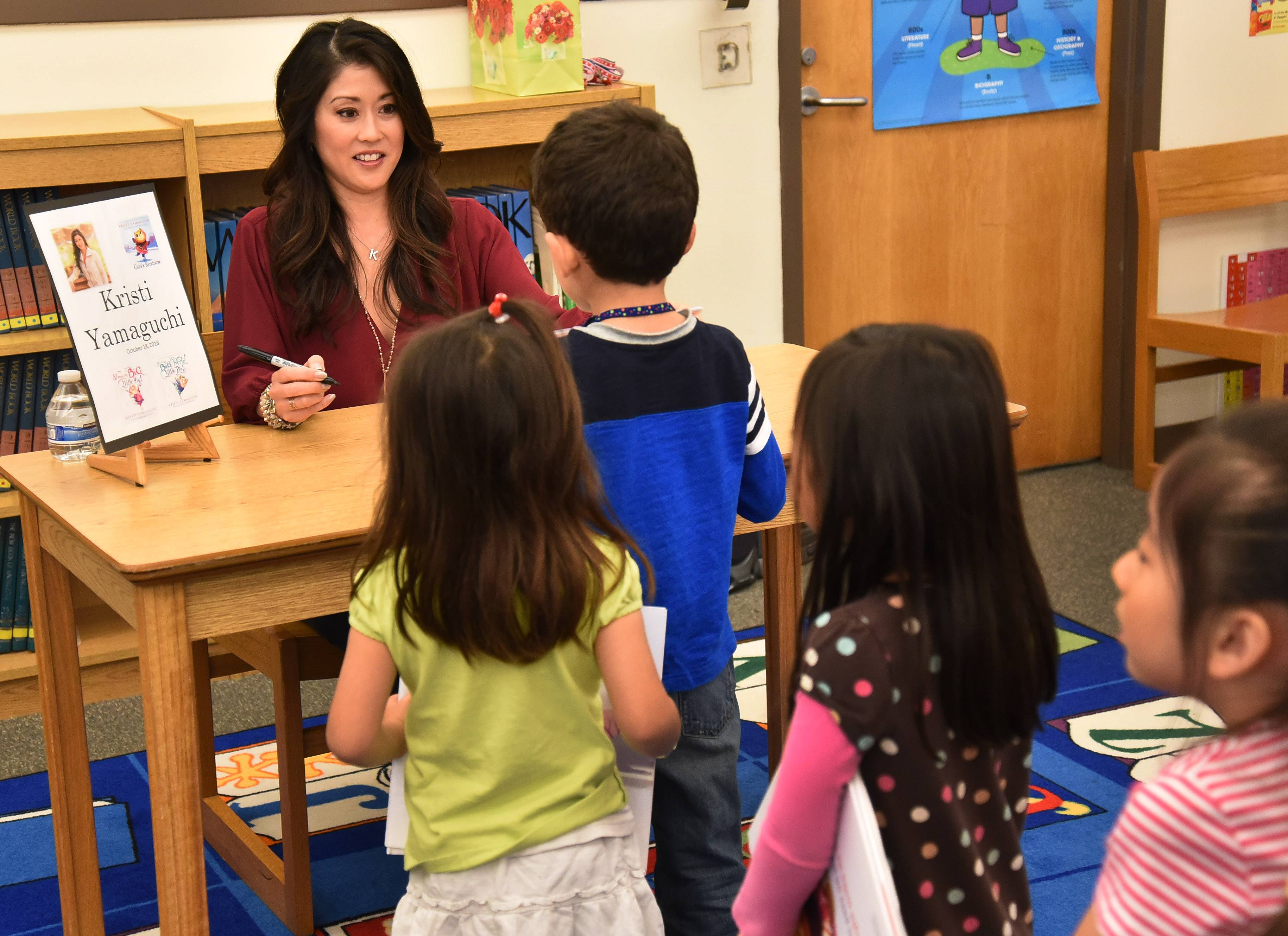 "Olympic figure skater Kristi Yamaguchi signs her latest children's book, ""Cara's Kindness,"" for students Tuesday at Frank C. Whiteley School in Hoffman Estates. Proceeds from the book benefit early childhood literacy efforts."