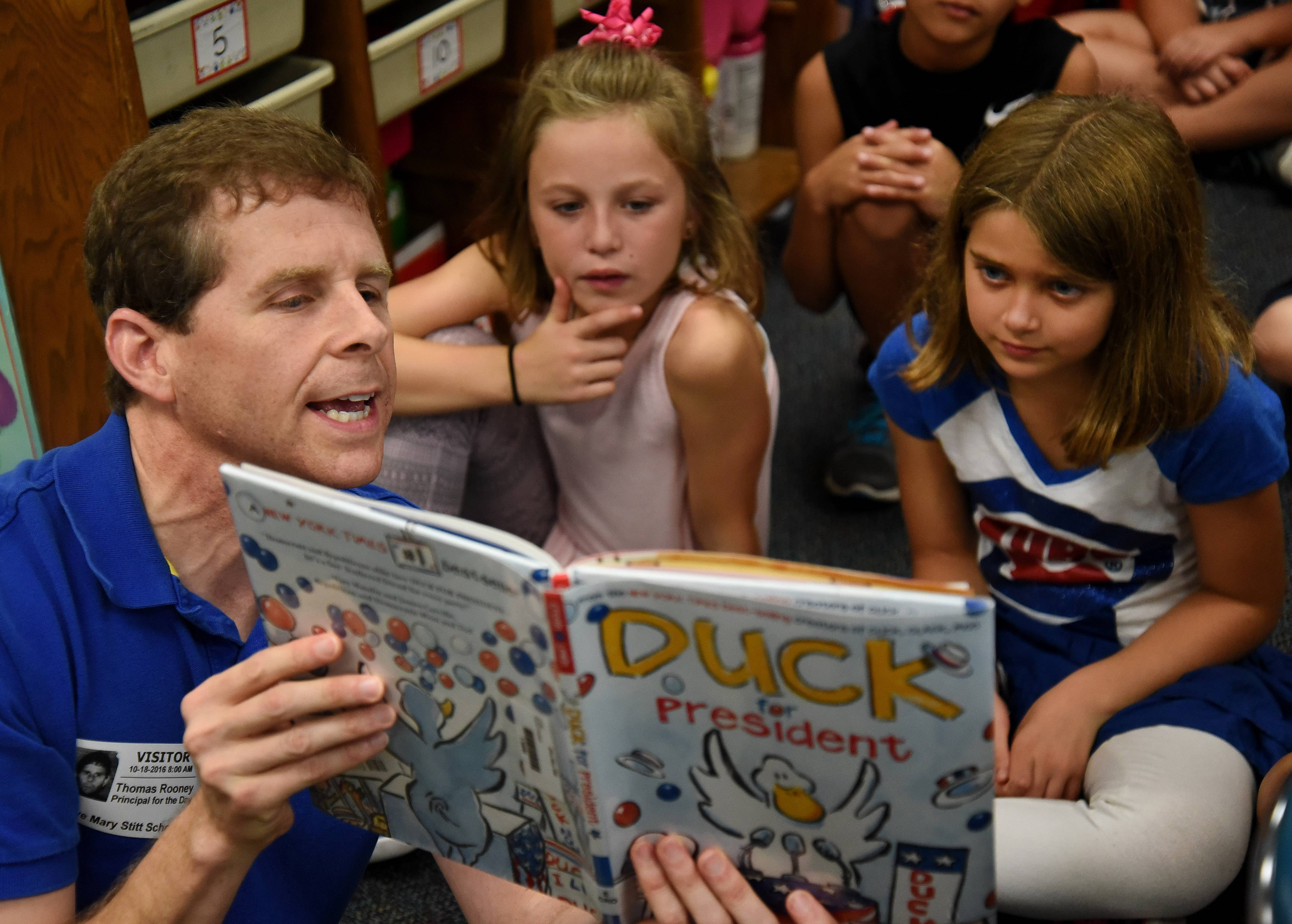 "State Sen. Tom Rooney reads ""Duck for President"" to Macey Teuscher, left, Sophia Harwood, right, and their fellow third graders, while serving as principal for the day Tuesday at Olive-Mary Stitt Elementary School in Arlington Heights."