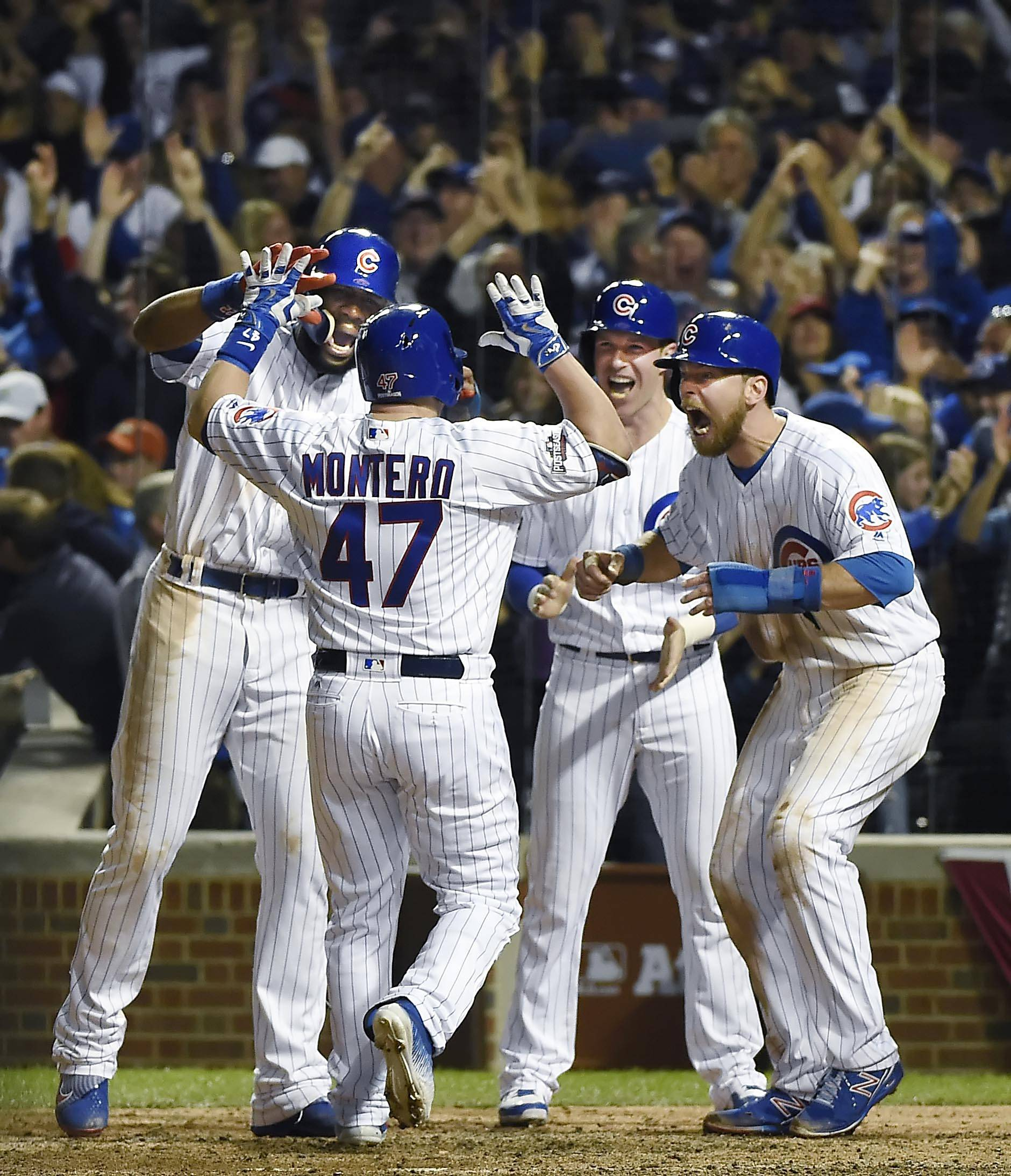 Cubs pinch-hitter Miguel Montero is met at home plate by teammates Jason Heyward, Chris Coghlan and Ben Zobrist after his grand slam in the bottom of the eighth inning Saturday against the Los Angeles Dodgers in Game 1 of the National League championship series at Wrigley Field.