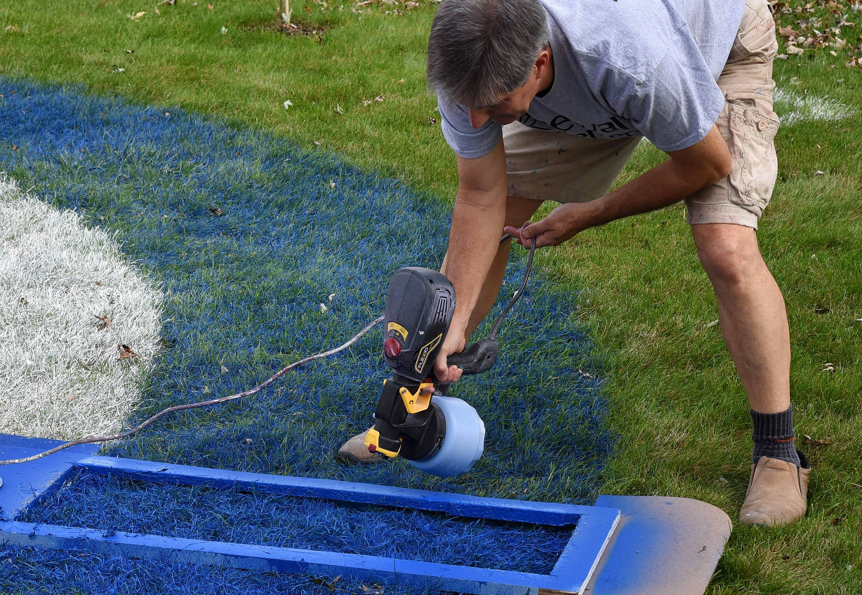 Jim McNamara of Hoffman Estates uses a special jig to retouch the 27-foot-diameter Cubs logo on his front lawn. It took more than 10 hours to paint the logo, and every rainfall requires a three-hour touch-up.