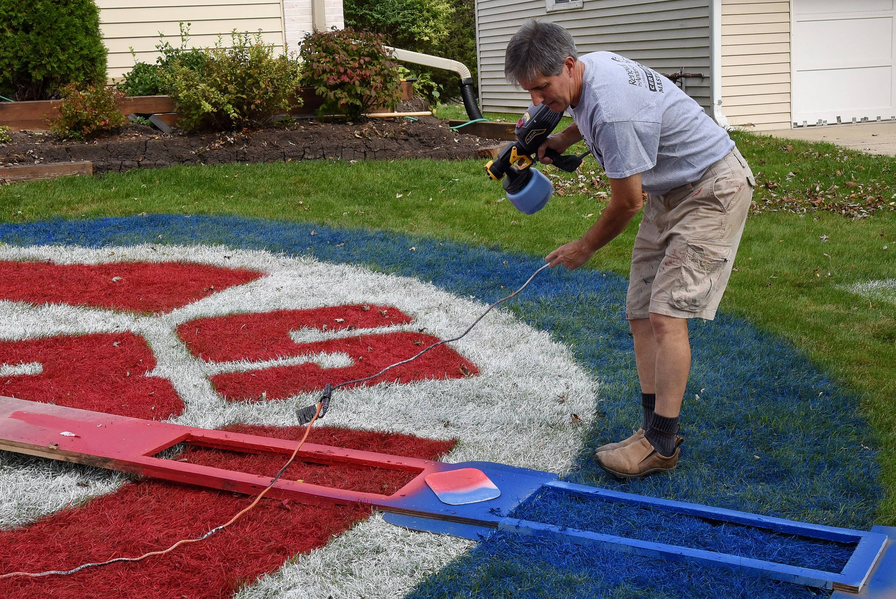 Jim McNamara of Hoffman Estates retouches the 27-foot-diameter Cubs logo on his front lawn Wednesday. McNamara admits his neighbors think he's a little nuts.