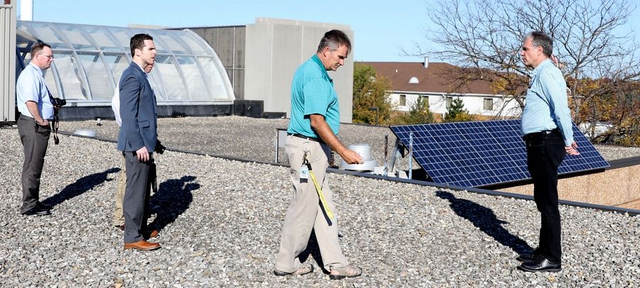 Jacobs High School Green Eagles club sponsor and environmental science teacher Robert Frazier, center, Tuesday discusses solar panels the club secured, which are expected to generate 2 percent of the electricity needed to run the Algonquin school.
