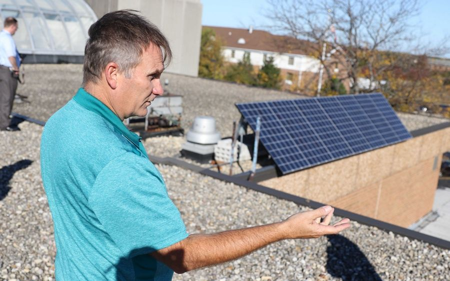 Jacobs High School environmental science teacher Robert Frazier Tuesday discusses solar panels that the school's Green Eagles club secured through a $7,000 grant from the Illinois Clean Energy Community Foundation.