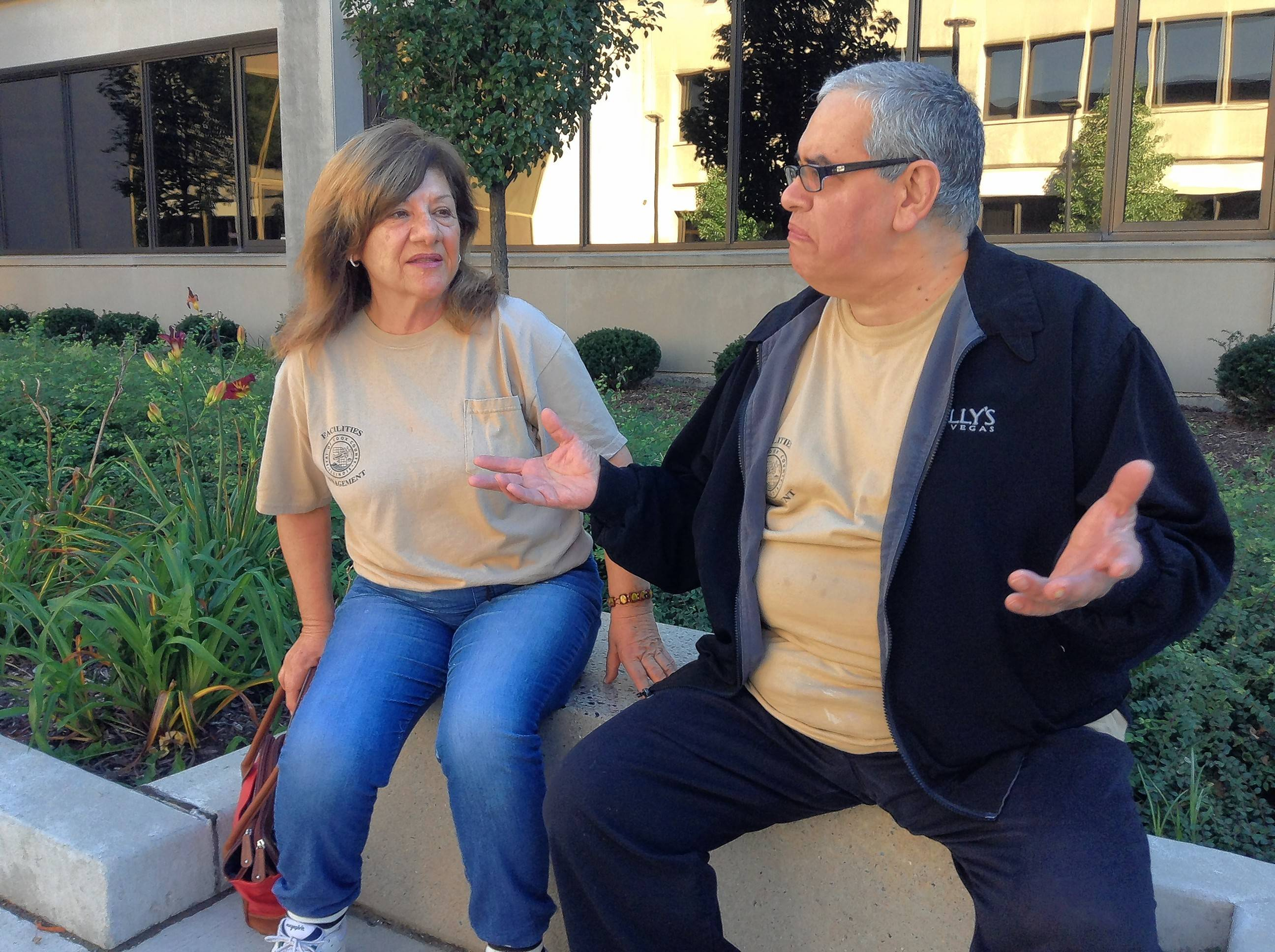 Outside the Rolling Meadows courthouse, co-workers Jim Stavrou and Georgia Charalambous discuss the Cubs' curse of the billy goat and how they might have played a part in lifting it.