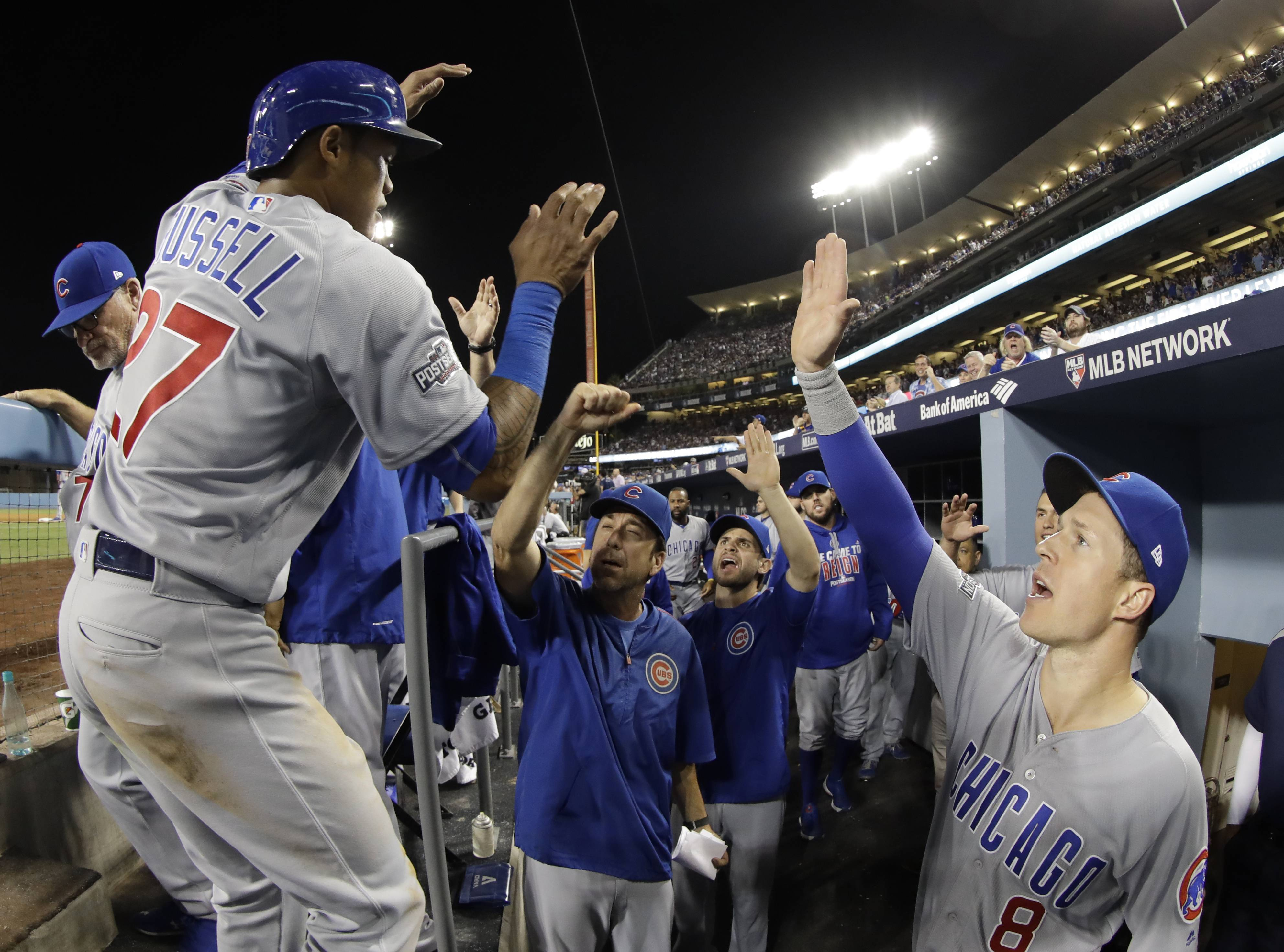 Chicago Cubs' Addison Russell is congratulated after scoring during the eighth inning of Game 5 of the National League baseball championship series against the Los Angeles Dodgers Thursday, Oct. 20, 2016, in Los Angeles.