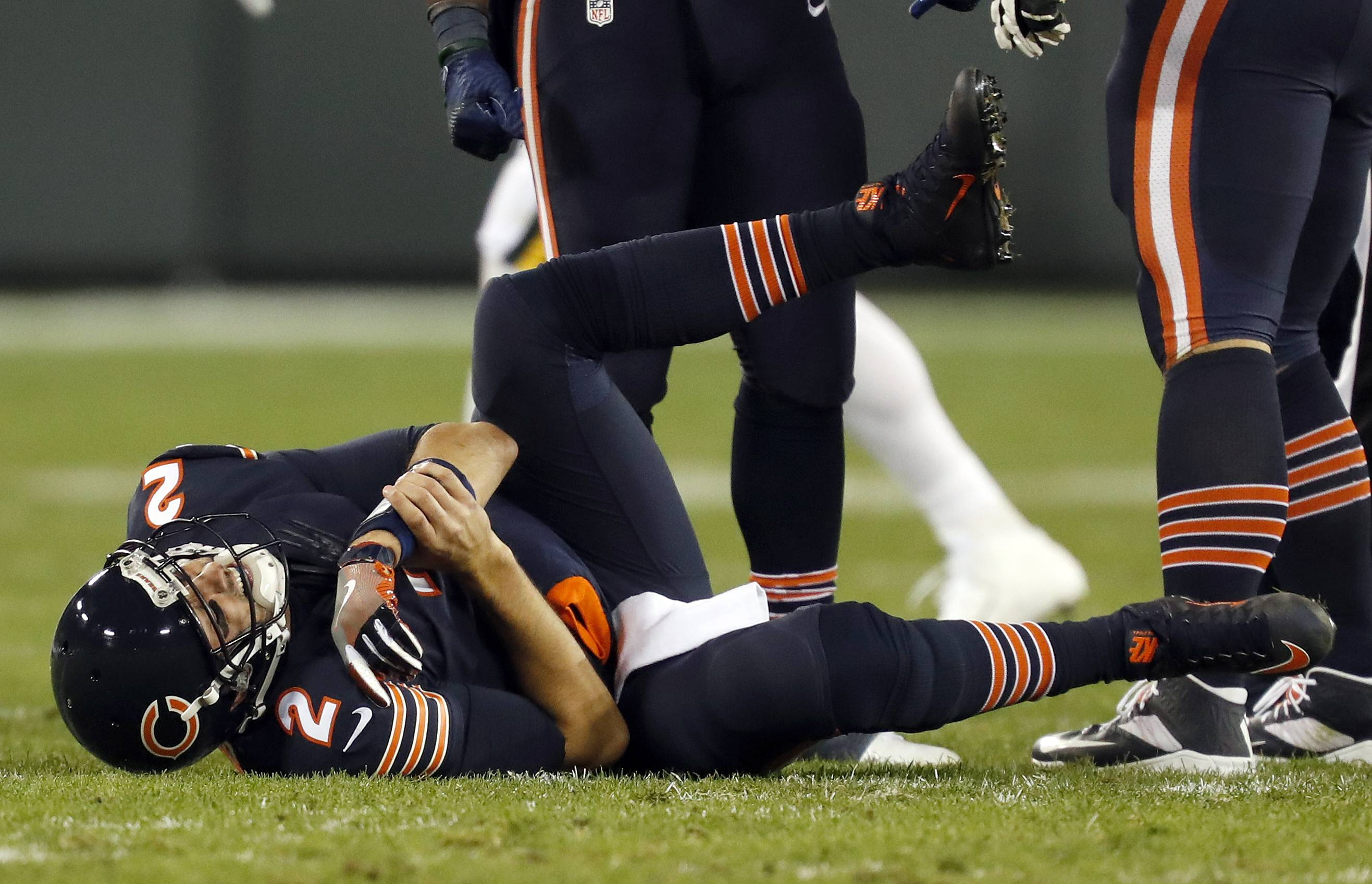Chicago Bears quarterback Brian Hoyer (2) holds his arm after getting tackled between Green Bay Packers outside linebacker Clay Matthews (52) and outside linebacker Julius Peppers (56) as he throws the ball during the first half of an NFL football game, Thursday, Oct. 20, 2016, in Green Bay, Wis. Hoyer left the game after this play.