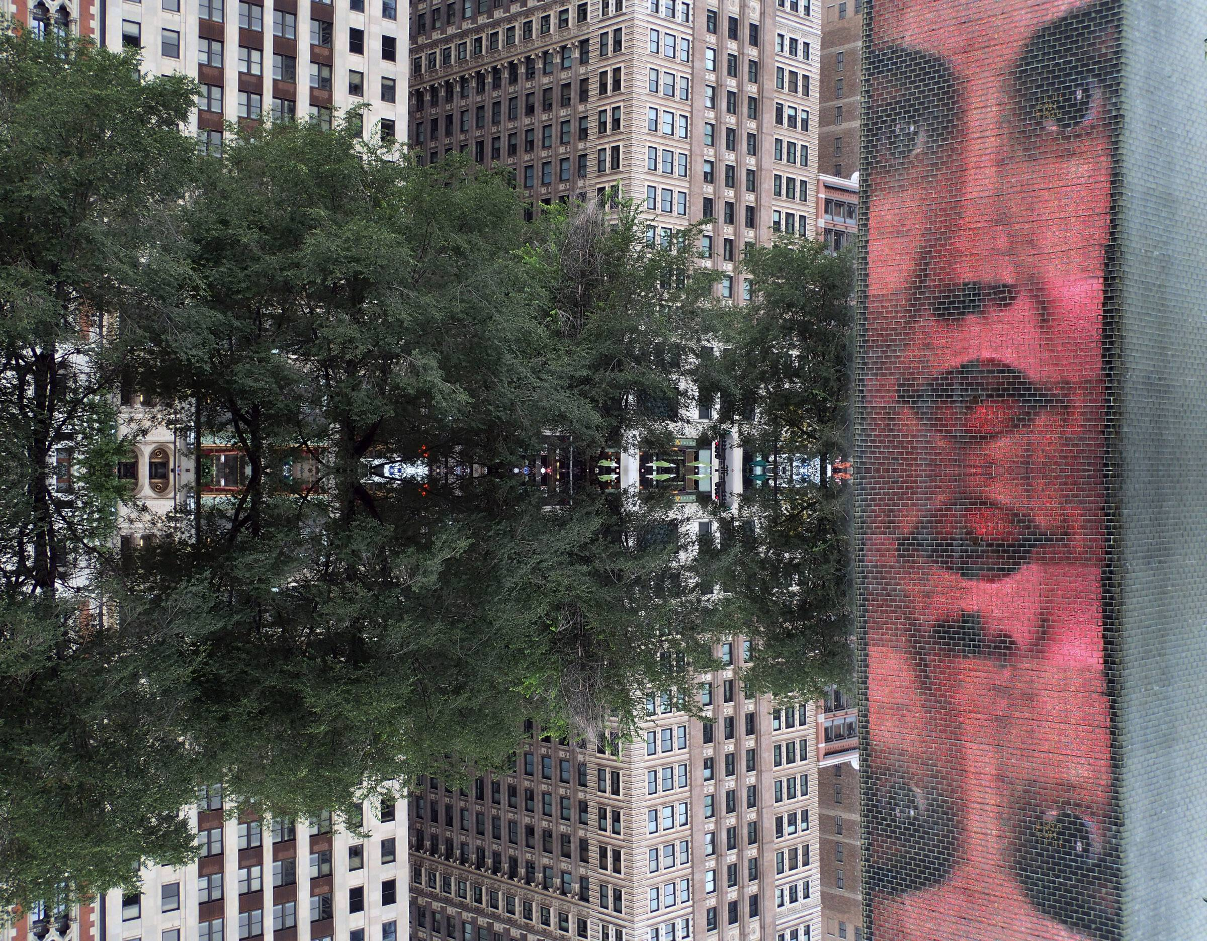 An unusual look with the face looking out toward the trees and buildings in a reflection of Crown Fountain in downtown Chicago.