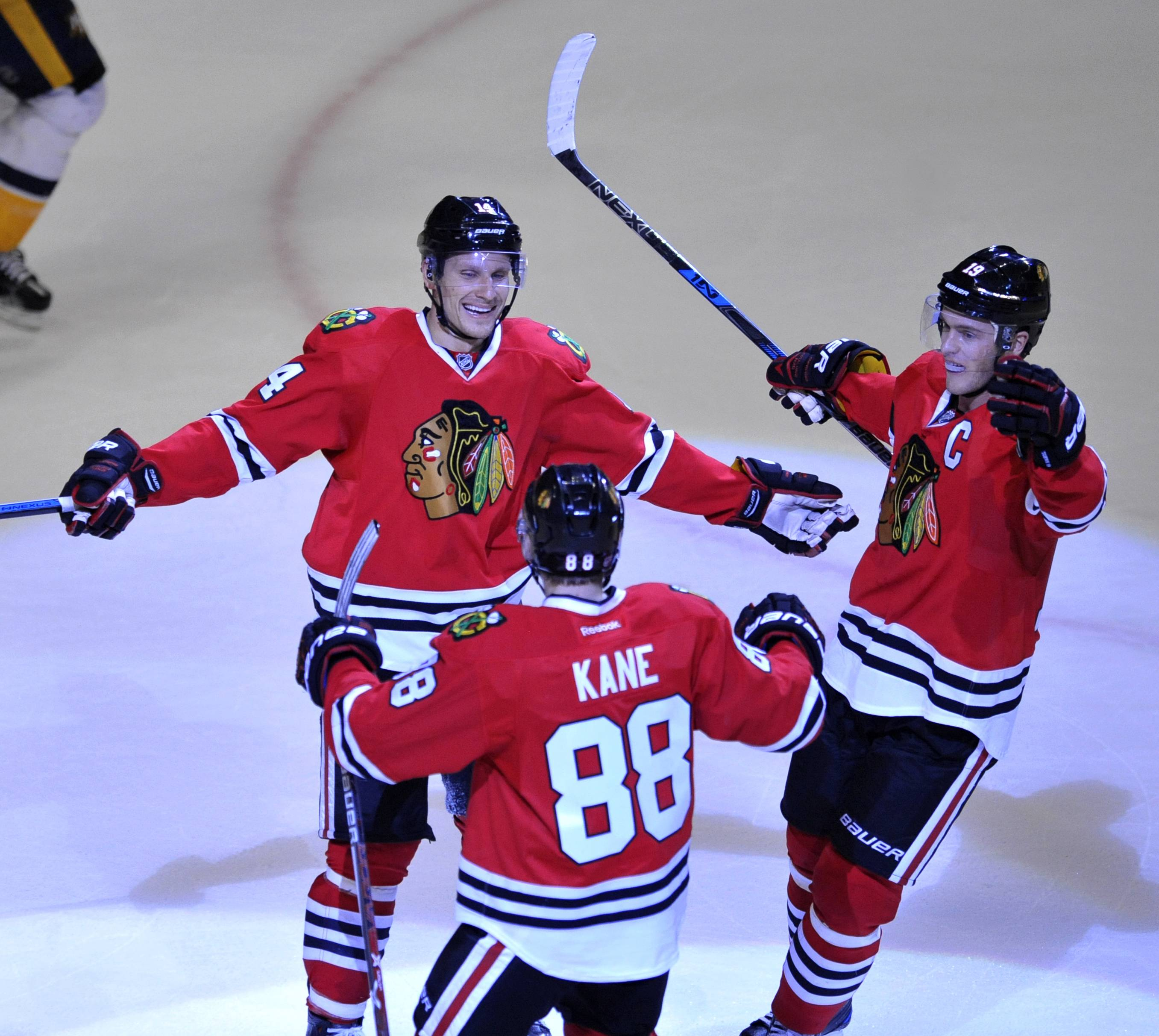 Chicago Blackhawks' Richard Panik (14), of Slovakia, celebrates with teammates Patrick Kane (88) and Jonathan Toews, right, after scoring a goal during the third period of an NHL hockey game against the Nashville Predators, Saturday, Oct. 15, 2016, in Chicago. (AP Photo/Paul Beaty)