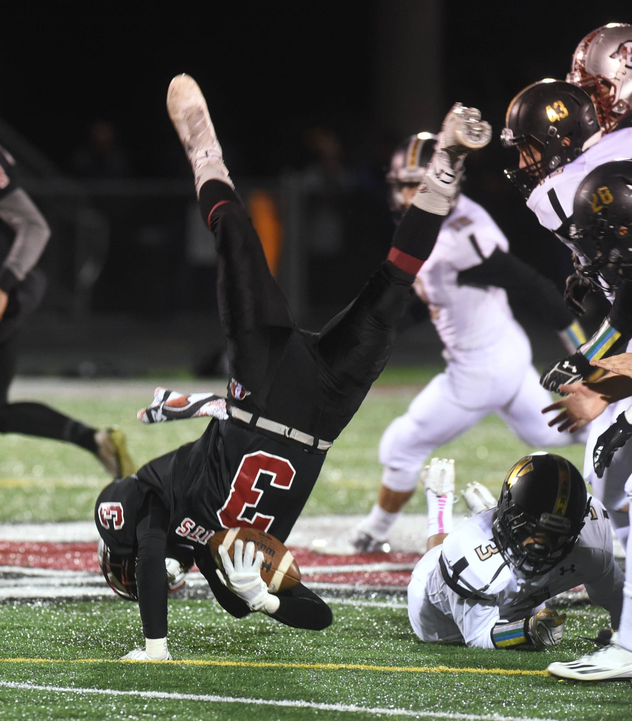 Antioch's Drew Porter (3) is upended as he runs the ball by Grayslake North's Sam Nayyer (3) during the first half of Friday's football game in Antioch.