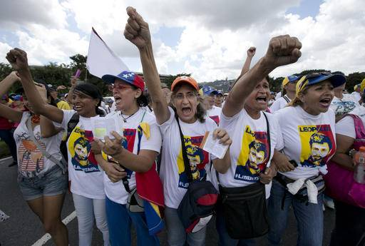 Woman wearing shirts showing the face of jailed opposition leader Leopoldo Lopez protest on a main street to demand a recall referendum against Venezuela's President Nicolas Maduro in Caracas, Venezuela, Saturday, Oct. 22, 2016. Venezuela is bracing for turbulence after the government blocked a presidential recall referendum in a move opposition leaders are calling a coup. The march was led by the wives of jailed activists. (AP Photo/Ariana Cubillos)