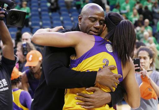 Los Angeles Sparks owner Magic Johnson, left, hugs Candace Parker after the Sparks won the WNBA basketball championship title with a win over the Minnesota Lynx, Thursday, Oct. 20, 2016, in Minneapolis. (AP Photo/Jim Mone)