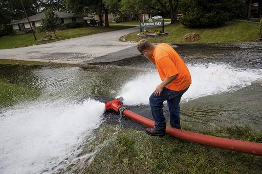 ADVANCE FOR USE SATURDAY, OCT. 22, 2016 AND THEREAFTER - In this Oct. 3, 2016 photo, Dustin Patterson checks a gauge measuring the amount of water spewing from a hydrant in Chatham, Ill. Chatham is performing its first system-wide, water-main flushing to clean the more than 130 miles of pipe and improve the water quality. (Ted Schurter/The State Journal-Register via AP)