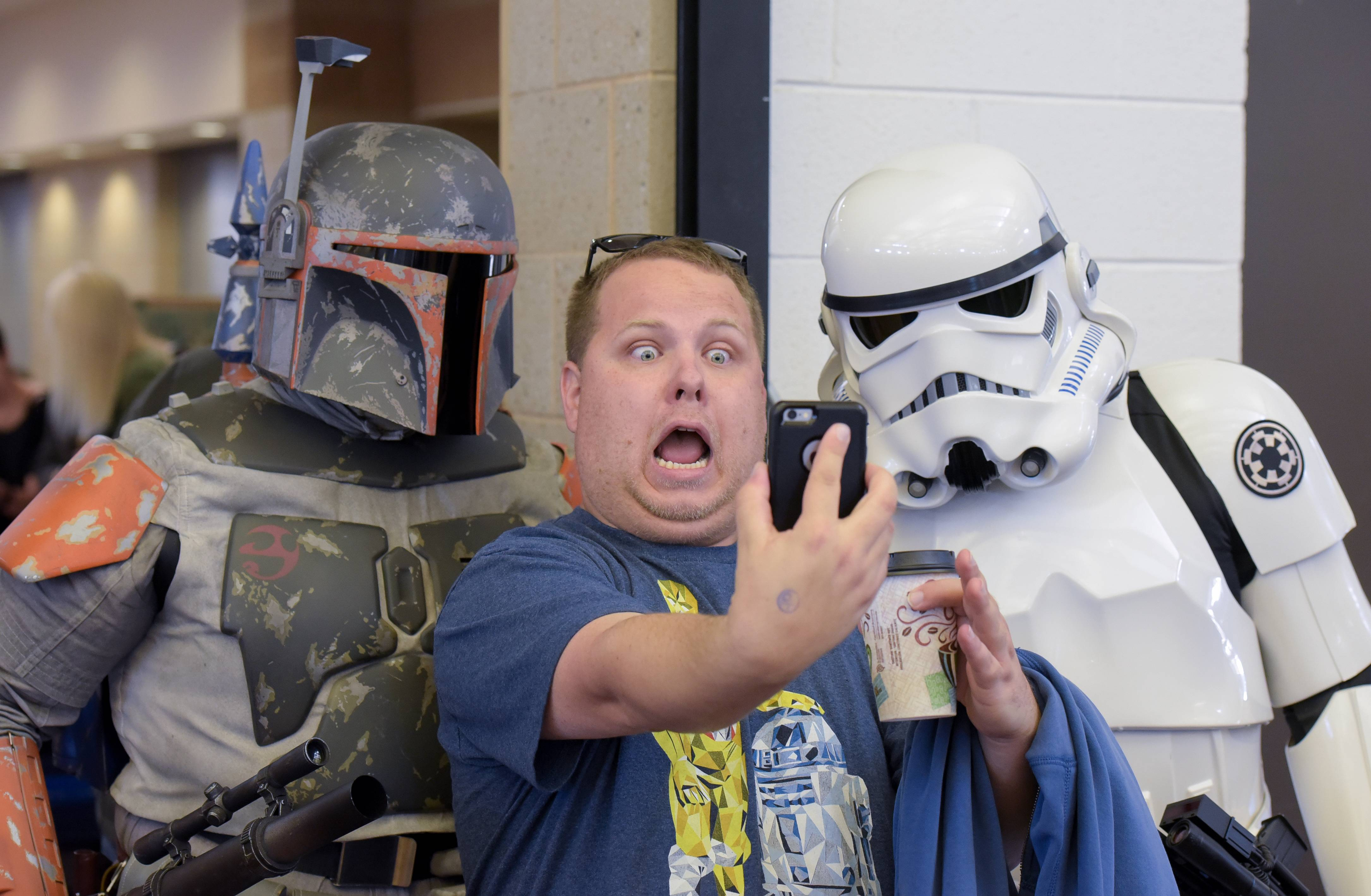 "Shane Donovan of Ottawa takes a selfie with Boba Fett and a Stormtrooper during the 43rd Antique Collectible Toy and Doll Show on Sunday at the Kane County Fair grounds. The characters were part of the Midwest Garrison of the 501st Legion, a ""Star Wars"" costuming organization."