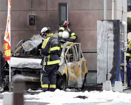 Firefighters investigate the scene where two cars caught on fire at a parking lot in Utsunomiya, north of Tokyo Sunday, Oct. 23, 2016. Police are investigating two apparent blasts, one at the parking lot and the other at a nearby public park, that happened back-to- back and left one person dead. (Yukie Nishizawa/Kyodo News via AP)