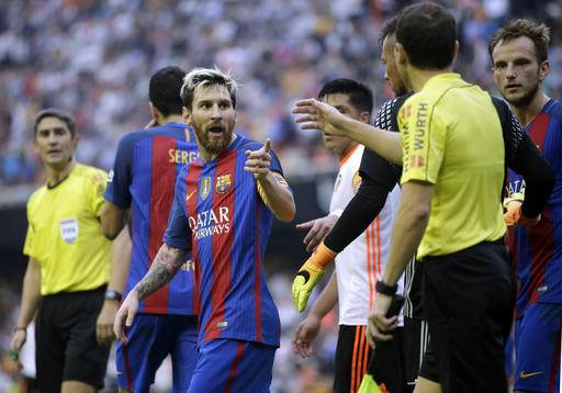 FC Barcelona's Lionel Messi, center, talks with the referee after the crowd threw objects on to the pitch during the Spanish La Liga soccer match between Valencia and FC Barcelona at the Mestalla stadium in Valencia, Spain, Saturday, Oct. 22, 2016. (AP Photo/Manu Fernandez)