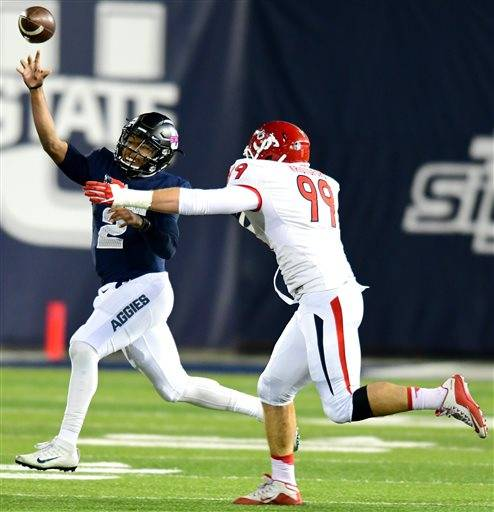 Utah State quarterback Kent Myers throws a pass as Fresno State's Nick Kristofors gives chase during an NCAA college football game, Saturday, Oct. 22, 2016, in Logan, Utah. (John Zsiray/Herald Journal via AP)