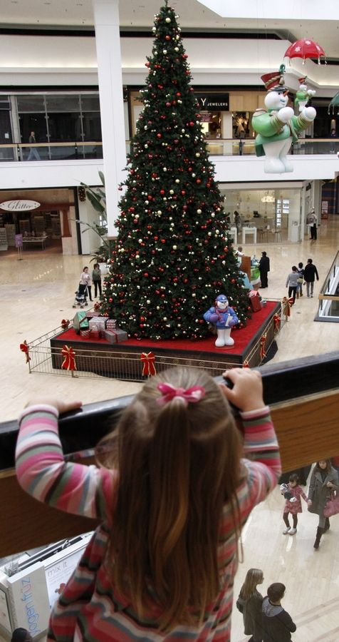 A little girl looks down at the Christmas tree at the Fox Valley Mall. The mall is closing on Thanksgiving Day and hopes to re-establish Black Friday as the holiday shopping kickoff.