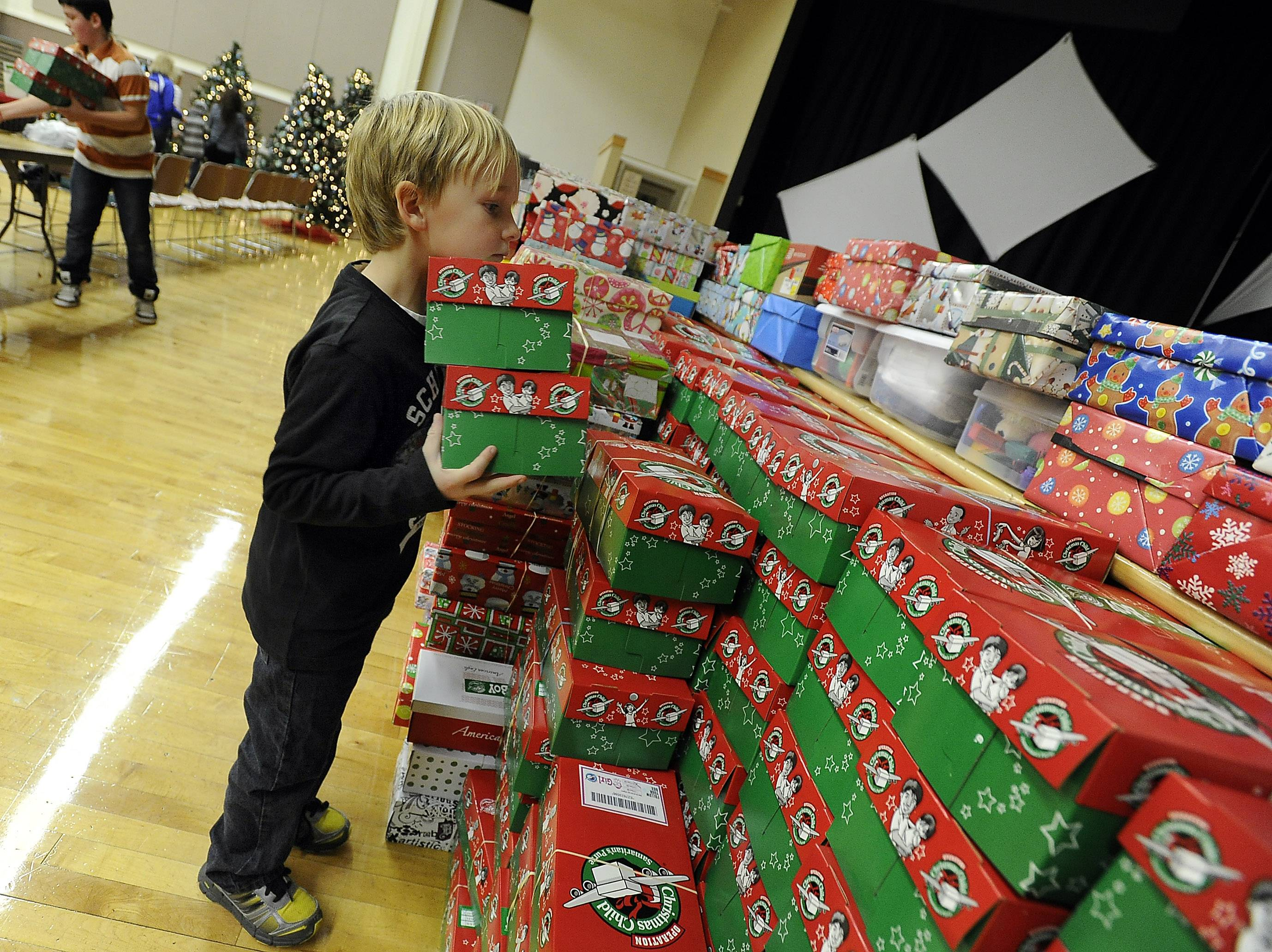 Grayson Peterson, 6, of Wisconsin stacks fully loaded boxes at an Operation Christmas Child collection event at Immanuel Church in Gurnee.