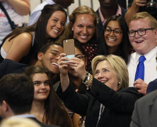FILE - In this June 21, 2016 file photo, Democratic presidential candidate Hillary Clinton takes a photo with supporters after speaking at Fort Hayes Vocational School in Columbus, Ohio. A new poll finds that young voters are starting to come through for Clinton, particularly among whites ages 18 to 30. In the final days of the campaign, Clinton is shored up what was once a troubling weakness in a key voting bloc, a sign of strength that helps explain how the former secretary of state may be able to expand her campaign into traditionally Republican states. (AP Photo/Jay LaPrete, File)