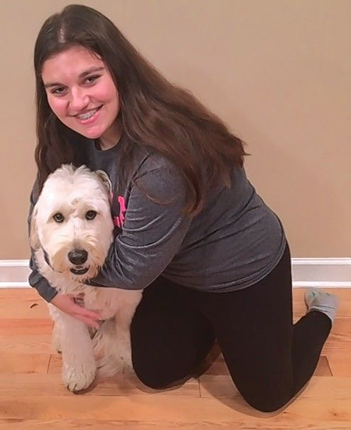 Nicole Relias, a junior at Buffalo Grove High School, is with her 4-year old dog, Bella. It was Bella getting skunked that led to Relias and her classmates forming a startup company to provide de-skunking kits for dogs.
