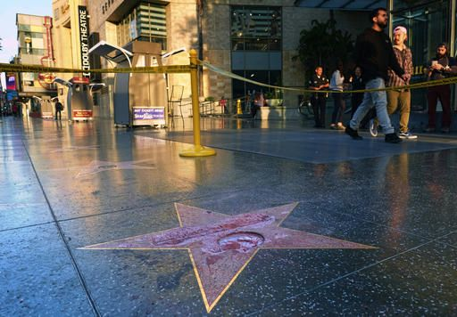 Pedestrians walk past a cordoned off area surrounding the vandalized star for Republican presidential candidate Donald Trump on the Hollywood Walk of Fame, Wednesday, Oct. 26,2016, in Los Angeles. Det. Meghan Aguilar said investigators were called to the scene before dawn Wednesday following reports that Trump's star was destroyed by blows from a hammer.