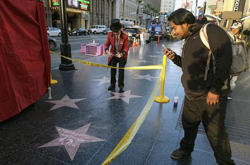 A man takes a photo of the vandalized star for Republican presidential candidate Donald Trump on the Hollywood Walk of Fame, Wednesday, Oct. 26, 2016, in Los Angeles. Det. Meghan Aguilar said investigators were called to the scene before dawn Wednesday following reports that Trump's star was destroyed by blows from a hammer.