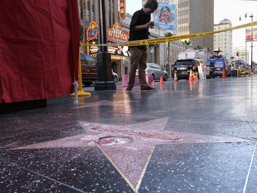 A man stands near a cordoned off area surrounding the vandalized star for Republican presidential candidate Donald Trump on the Hollywood Walk of Fame, Wednesday, Oct. 26, 2016, in Los Angeles. Det. Meghan Aguilar said investigators were called to the scene before dawn Wednesday following reports that Trump's star was destroyed by blows from a hammer.