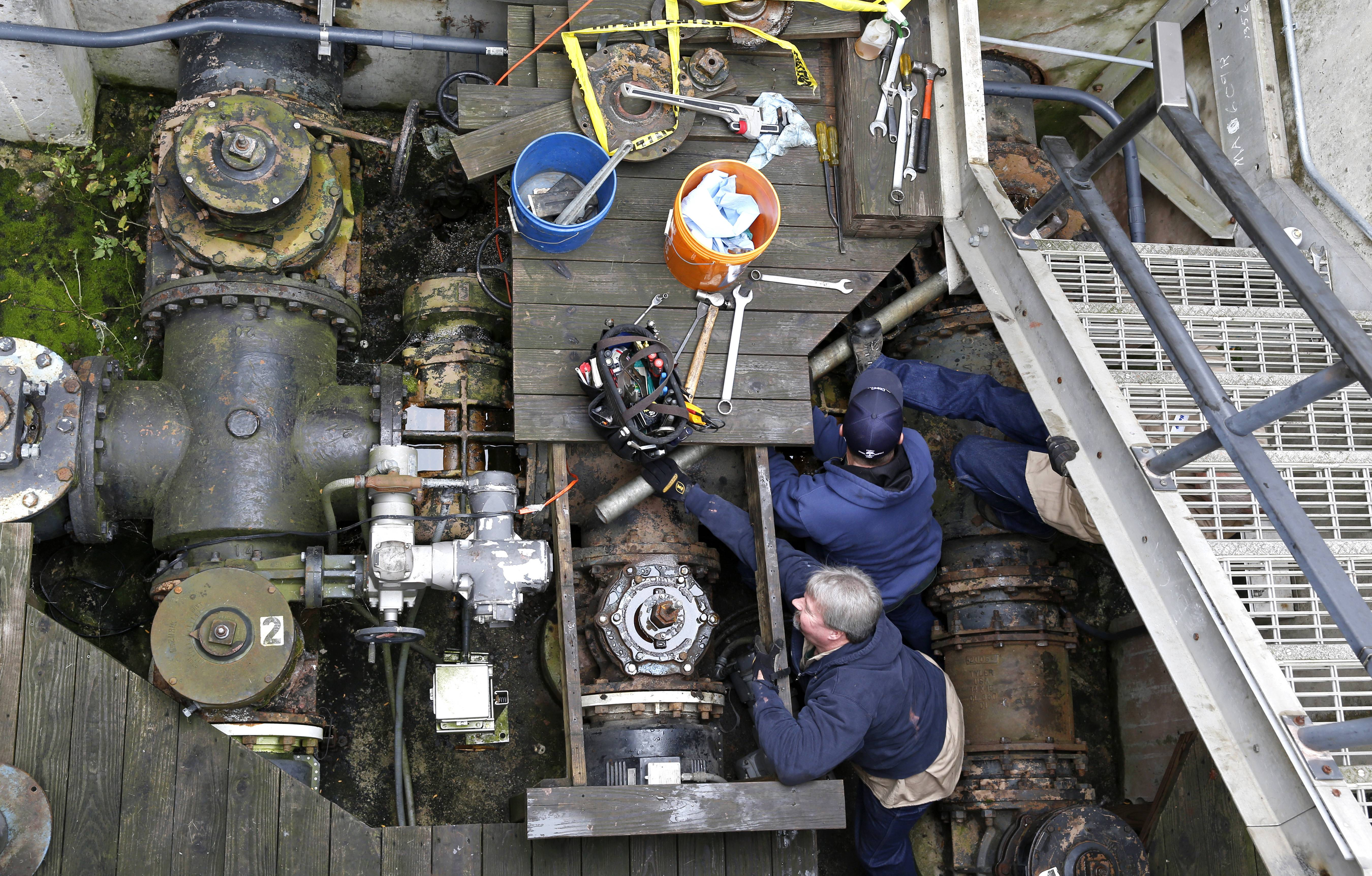 Employees at Naperville's Springbrook Water Reclamation Center change a 40-year-old valve in a solids return line at the facility where wastewater is processed and then released into the Lower DuPage River.