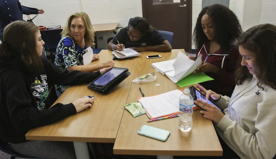 Glenbard South Principal Sandra Coughlin works with sophomore Melissa Marlovitz, from left, sophomore Armania Wilson, senior Shelly Smith and junior Julia Cangonji during their lunch break in the new AP Student Center at the Glen Ellyn school.